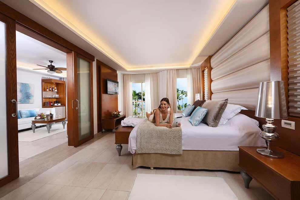 Family-Club-One-Bedroom-Suite-bed-woman
